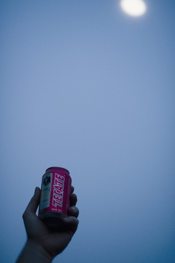 Stock Photo: 4176-36697 A can of Tecate beer held aginst the moon.
