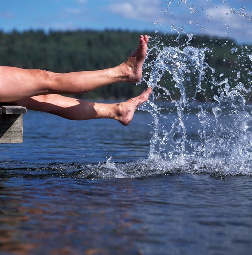 Low section view of a person splashing water : Stock Photo