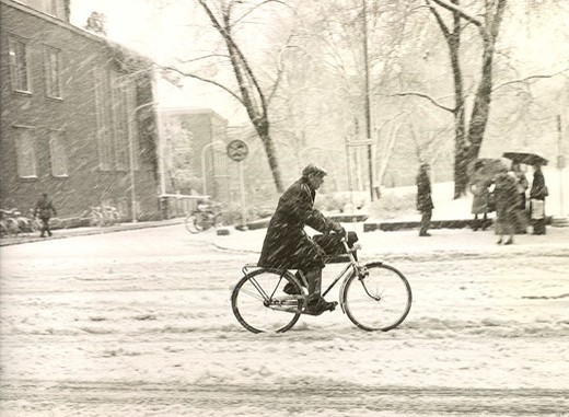 Side profile of a man riding bicycle in a snowstorm : Stock Photo