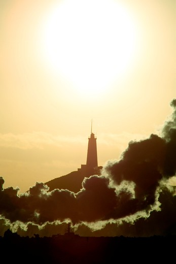 Lighthouse upon a hill, smoke in front of it and bright sun and golden sky behind it : Stock Photo