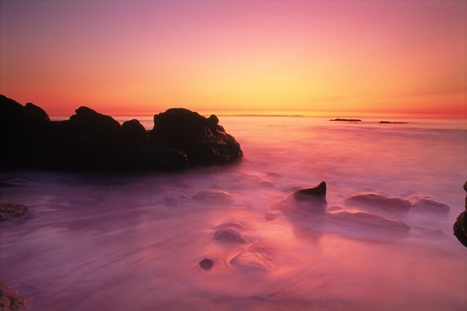 Waves painting rocks and sandy shore at sunset : Stock Photo