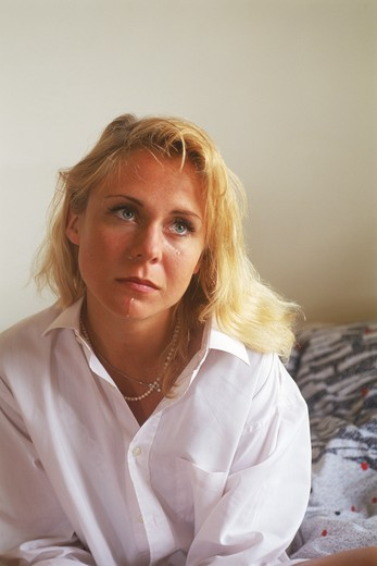 Woman sitting on bed crying : Stock Photo