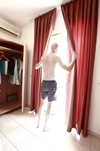 Young man opening curtains at a hotel, Thassos Island, Greece (Grekland). : Stock Photo
