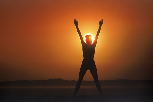 Woman silhouetted by sun in victory posture : Stock Photo