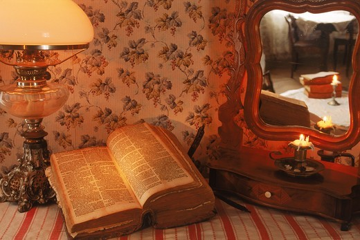 Old Bible sitting on antique bureau under lamp : Stock Photo