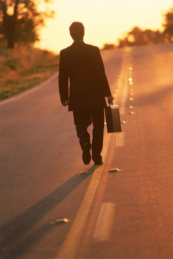 Businessman with briefcase walking endless highway at dawn : Stock Photo