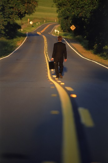Businessman walking on country road with briefcase at dawn : Stock Photo