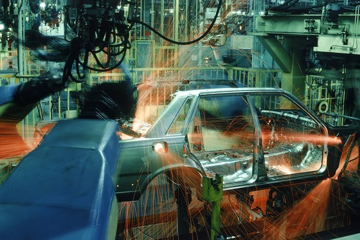 Sparks flying from spot welding robotics at automobile factory : Stock Photo