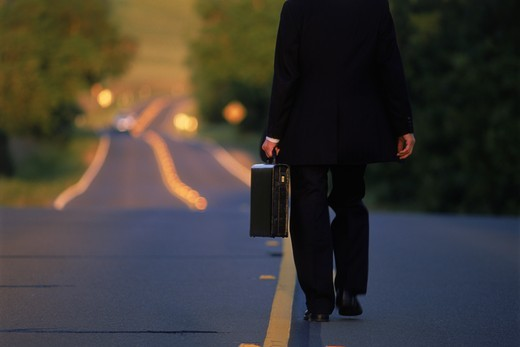 Businessman with briefcase alone on yellow lined country road : Stock Photo