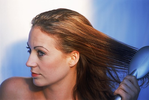 Stock Photo: 4176-6526 Woman brushing brunette hair after shower
