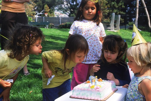 Kids at birthday party blowing out candles : Stock Photo