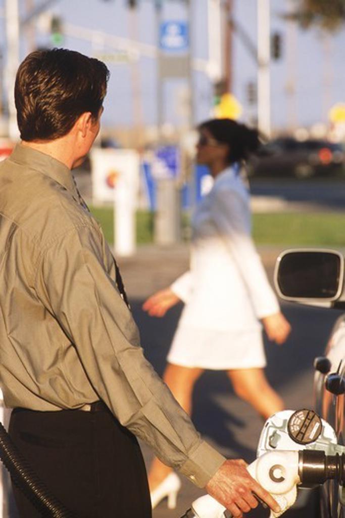 Man at gas pump watching passing woman : Stock Photo