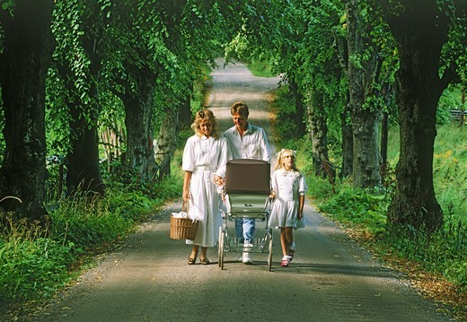 Baby in carriage leading family of four on country road : Stock Photo