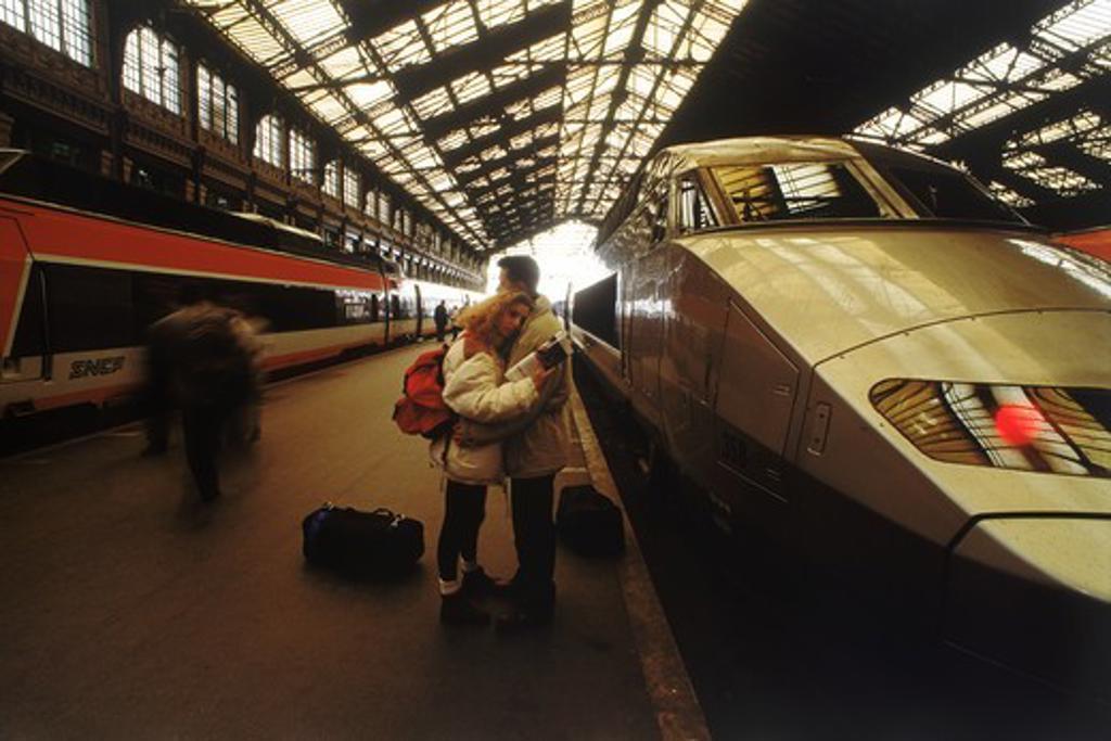 Couple saying goodbye next to SNCF high speed train at Gare du Lyon in Paris : Stock Photo