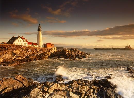 Ship passing Portland Head Lighthouse on coast of Maine at sunrise : Stock Photo