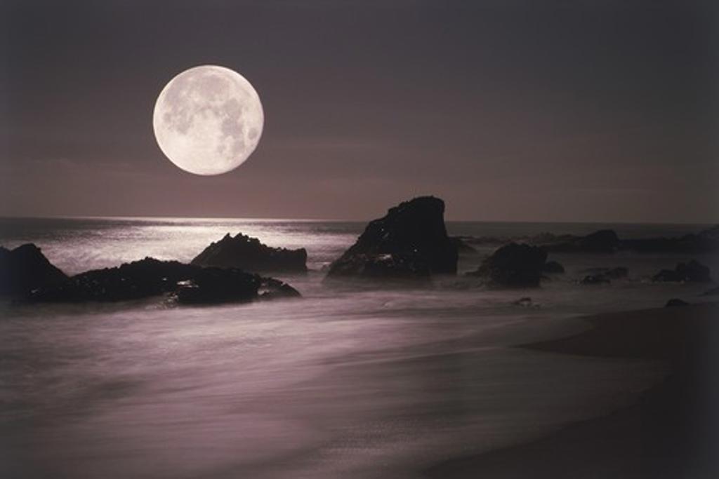 Moon setting over rocky shore : Stock Photo
