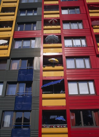 Low angle view of colourful apartment building with umbrellas and glass windows : Stock Photo