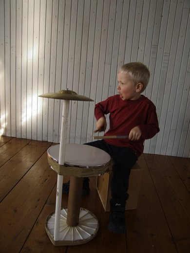 A five-year-old boy beating a toy drum. Sweden : Stock Photo