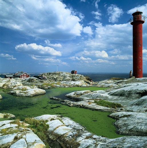 Stock Photo: 4176-9780 Red lighthouse at the coast and clouds on the horizon
