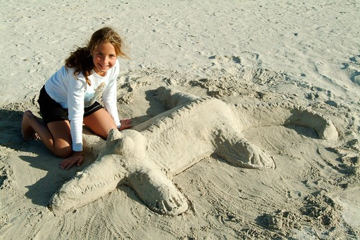 A girl with sand crocodile on the beach : Stock Photo