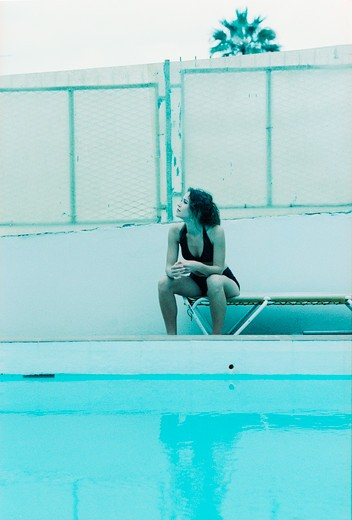 Stock Photo: 4176-9910 A woman sitting by the swimming pool