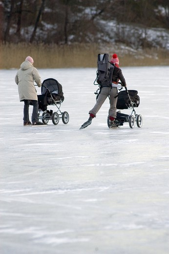 Stock Photo: 4177R-2172 Rear view of two women ice-skating with their baby strollers