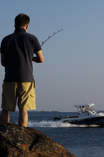 Stock Photo: 4177R-2546 Rear view of a man fishing and boat in background