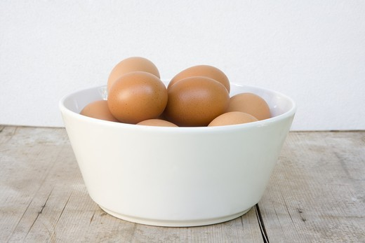 White bowl with brown eggs standing on wooden board : Stock Photo