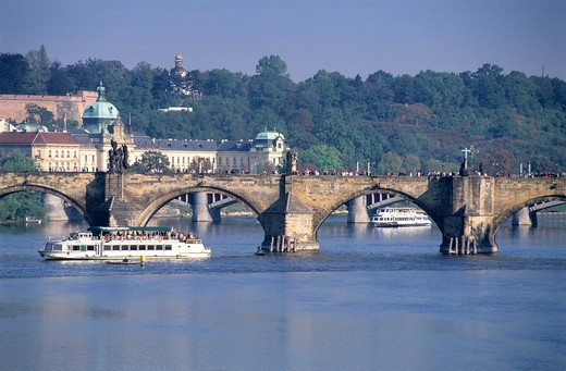 A boat sailing by the Charles Bridge in Prague, Czech Republic : Stock Photo
