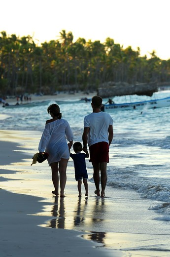 Family taking a walk on a sandy beach of tropical resort : Stock Photo