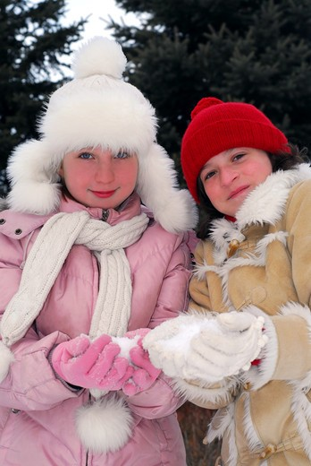 Portrait of two young girls in winter park holding snowballs : Stock Photo