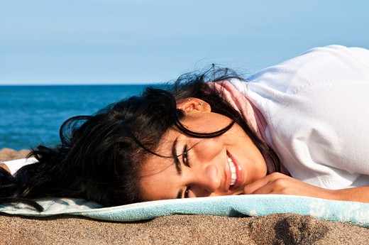 Portrait of beautiful smiling native american girl laying at beach : Stock Photo