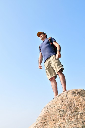 Stock Photo: 4183R-1564 Middle aged hiker standing on top of a mountain