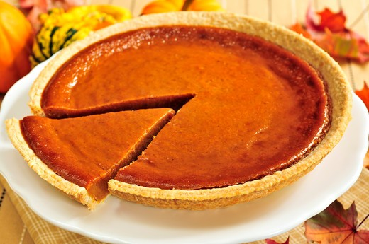 Whole pumpkin pie with a slice cut out : Stock Photo