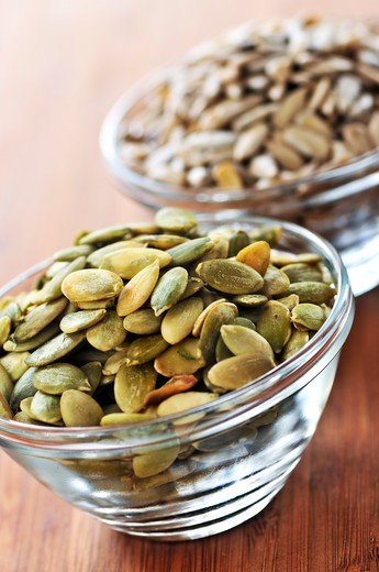 Pumpkin and sunflower seeds close up in glass bowl : Stock Photo