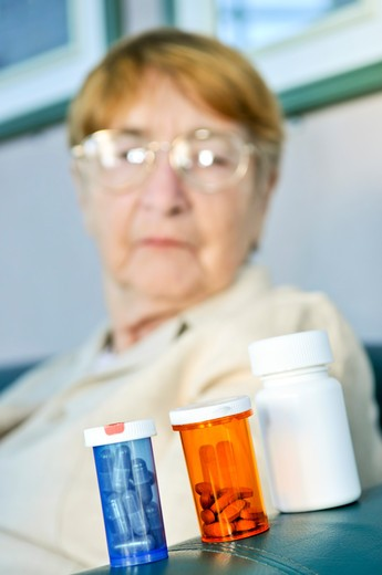 Elderly woman sitting and looking at pill bottles : Stock Photo