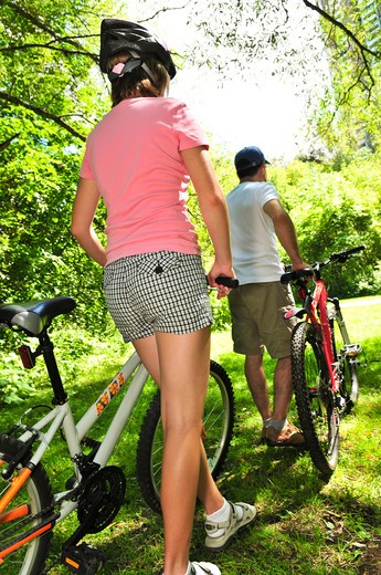 Stock Photo: 4183R-203 Teenage girl and her father with bicycles in summer park