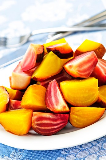 Roasted sliced red and golden beets on a plate : Stock Photo