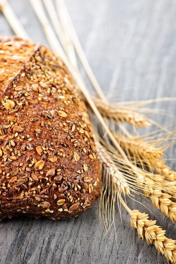 Stock Photo: 4183R-3361 Loaf of fresh baked multigrain bread with grain ears