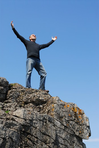 Stock Photo: 4183R-3747 A man standing on a cliff with his arms raised to the blue sky