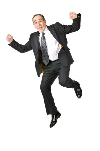 Jumping businessman in a suit isolated on white background : Stock Photo