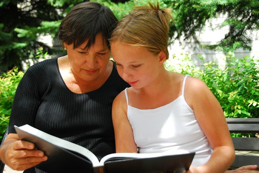 Grandmother and granddaughter reading a book : Stock Photo
