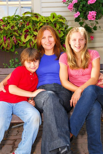 Portrait of a smiling family - mother and children - in front of the house : Stock Photo