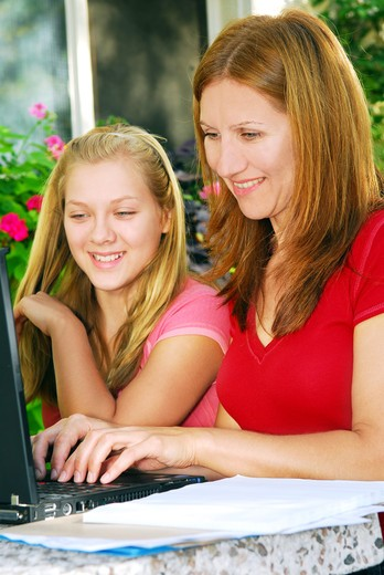 Mother and daughter working on computer at home in the backyard : Stock Photo
