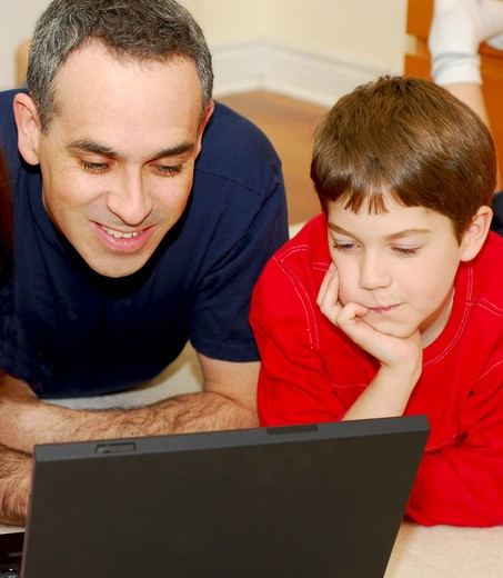 Father and son lying on the floor at home and looking into a portable computer : Stock Photo