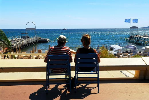 Stock Photo: 4183R-5573 Couple relaxing in chairs on Croisette promenade in Cannes, France
