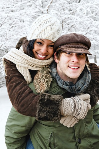 Portrait of couple having piggyback ride outdoors in winter : Stock Photo