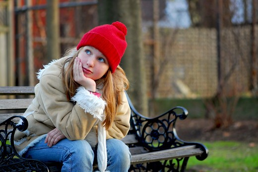Portrait of a young girl sitting on a bench : Stock Photo