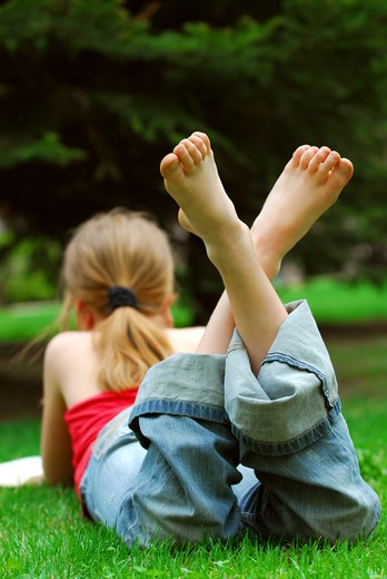 Stock Photo: 4183R-6068 Young girl relaxing with a book on green grass in a summer park