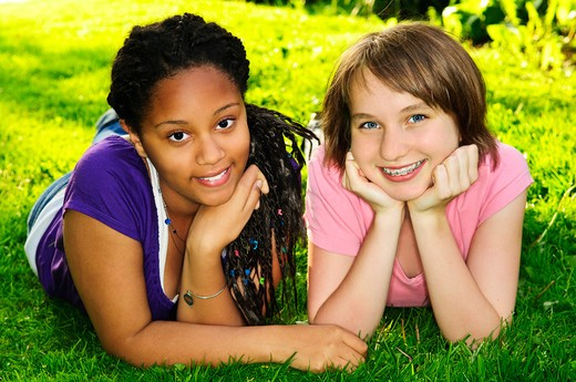Two happy teenage girls laying on grass : Stock Photo